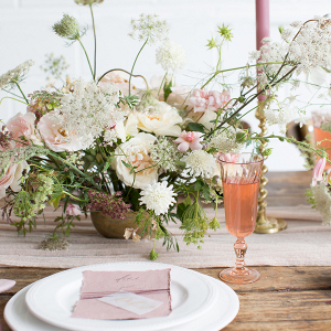 Blush pink table setting with a rustic fine art feel centrepiece of flowers stationery and candles