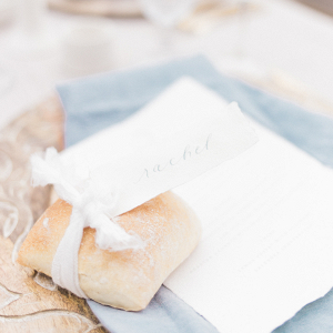 Delicate calligraphy place cards tied with silk ribbon to bread rolls for the place setting