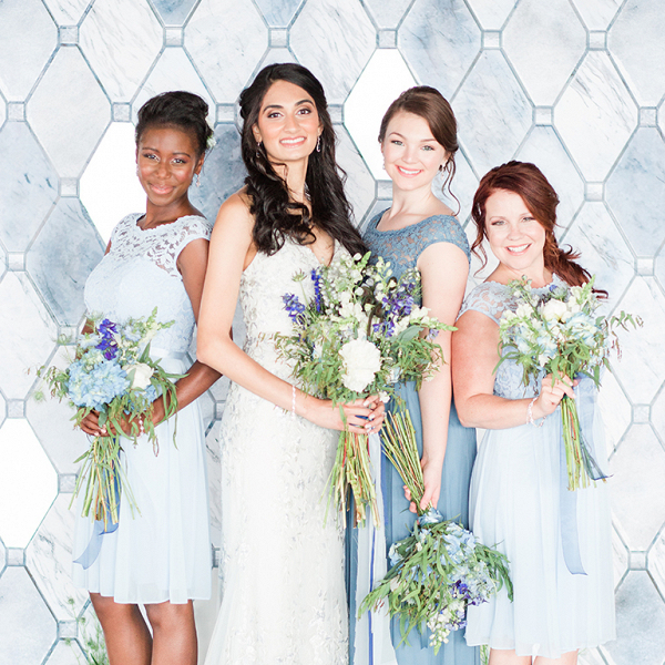 bride in lace wedding dress and bridesmaids in blue lace dresses with blue and white bouquets