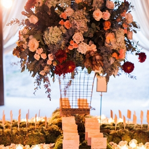 Romantic Candlelight, Fresh Moss, Rose Petals, and a Lush Elevated Floral Arrangement Decorate This Escort Card Display