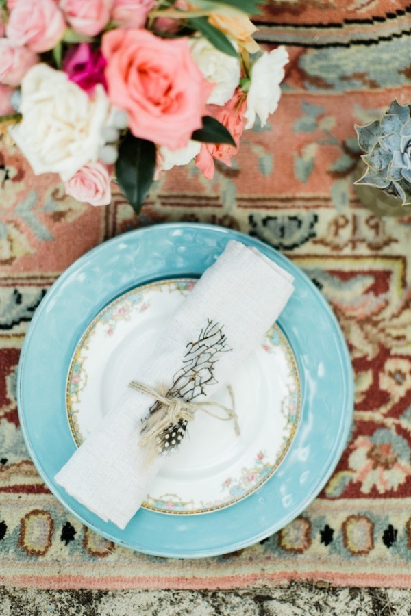 Boho place setting on a rug in a tent on a beach