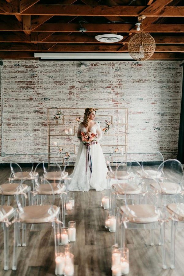 Vintage industrial wedding ceremony with ghost chairs