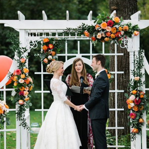 Outdoor wedding ceremony with orange floral arbor