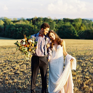 Couple in field with sunset glow on Chic Vintage Brides