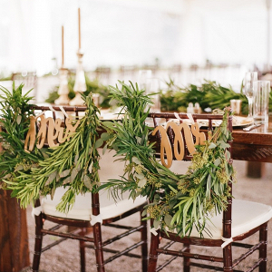 Sweetheart chairs decked in greenery and Mr and Mrs signs