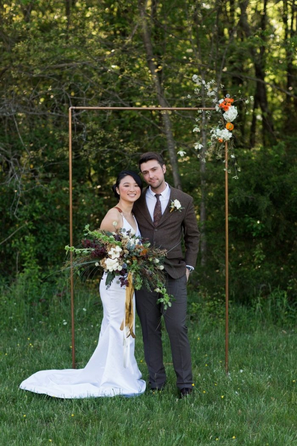 Outdoor wedding ceremony with copper pipe backdrop