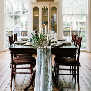Wedding table with trailing table runner and greenery