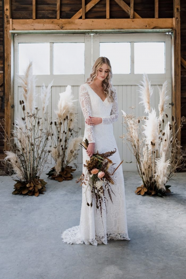 Fall bride with pampas grass ceremony backdrop