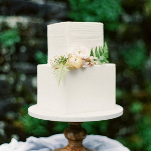 Ivory square wedding cake on a simple wooden cake stand