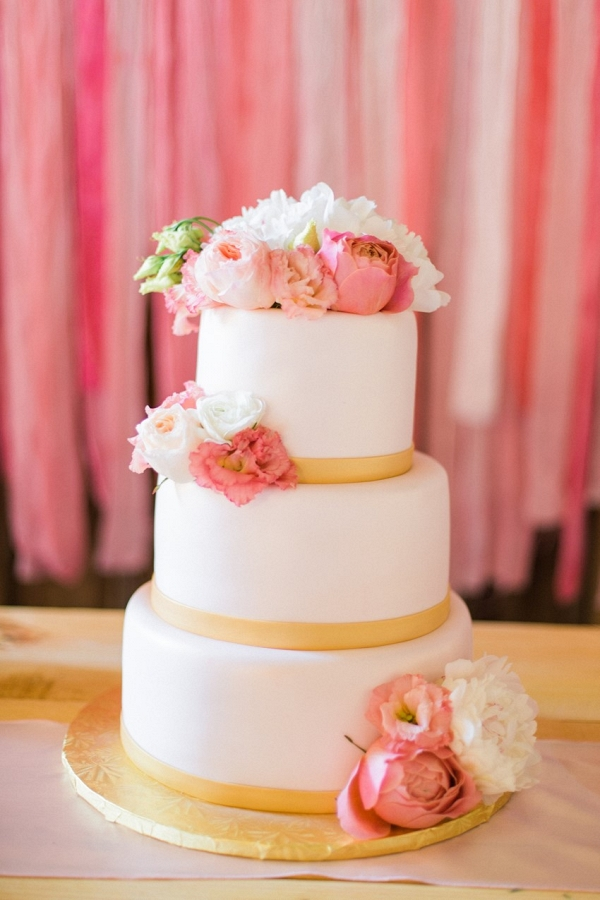 Pretty Flower Adorned Wedding Cake Against a Paper Backdrop