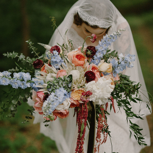 Vintage bride with lush red, blue, and peach bouquet