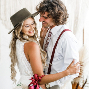 Boho bride in hat with groom in floral tie