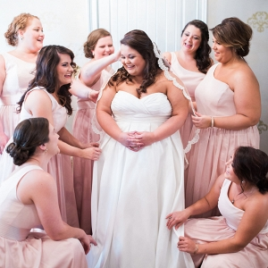 Bridesmaids Assisting Bride With Her Wedding Gown