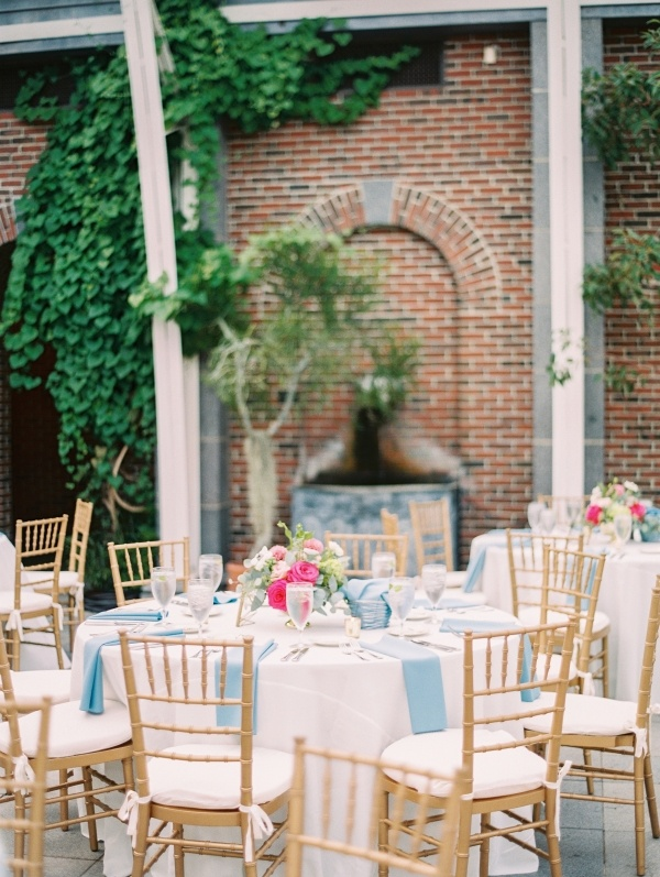 Outdoor wedding reception with hot pink floral centerpieces