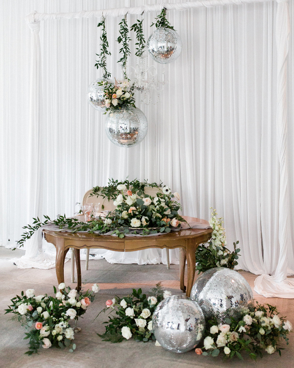 Sweetheart table with greenery and disco balls