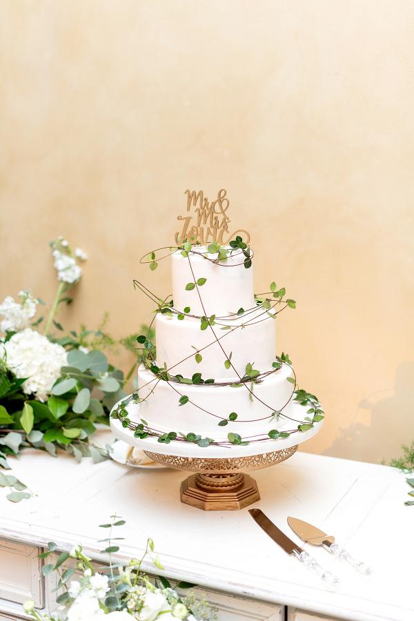 White wedding cake with draped greenery