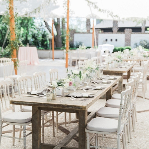 Romantic tented wedding reception with farm tables