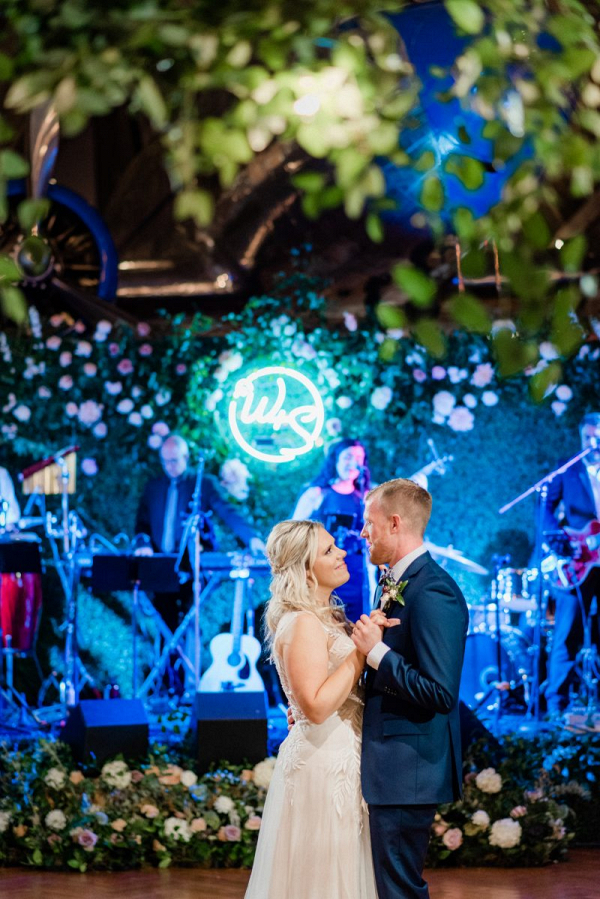 Wedding first dance in front of a blue neon sign