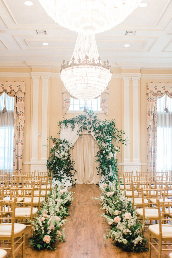 Elegant ballroom ceremony with floral arch and aisle