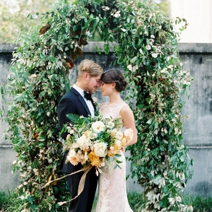 Couple in front of greenery arch on Elizabeth Anne Designs