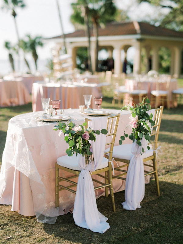 Sweetheart table with blush linens and greenery chair florals