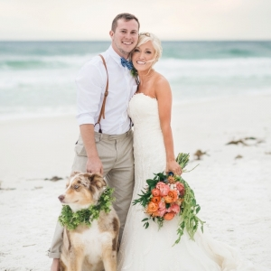 Bride and groom portrait on the beach with their dog