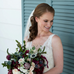 Bride holding burgundy bouquet