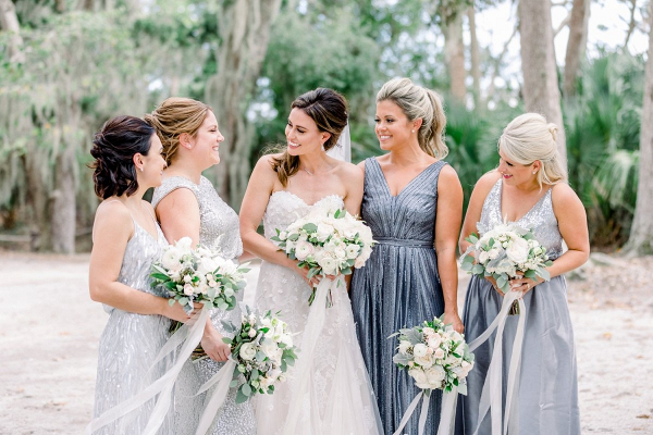 Bridesmaids in mismatched blue and silver dresses