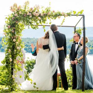 Jewish wedding ceremony under floral chuppah