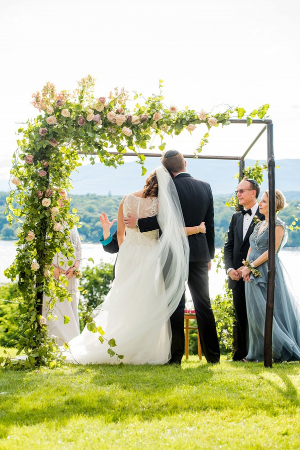 Jewish wedding ceremony under floral chuppah