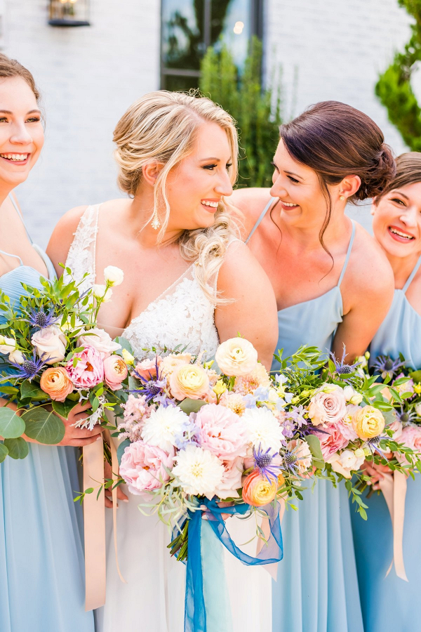 Blue bridesmaids with pastel bouquets