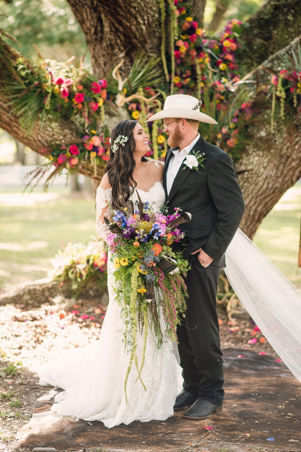 Country wedding ceremony with floral covered oak tree backdrop