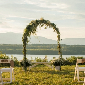 Outdoor ceremony arch adorned with flowers and greenery