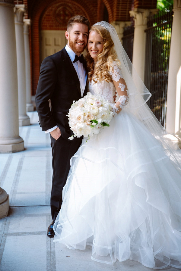 Classic bride in long sleeve lace and tulle gown with groom