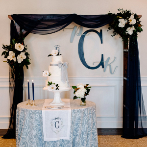 Classic southern wedding cake with monogram backdrop