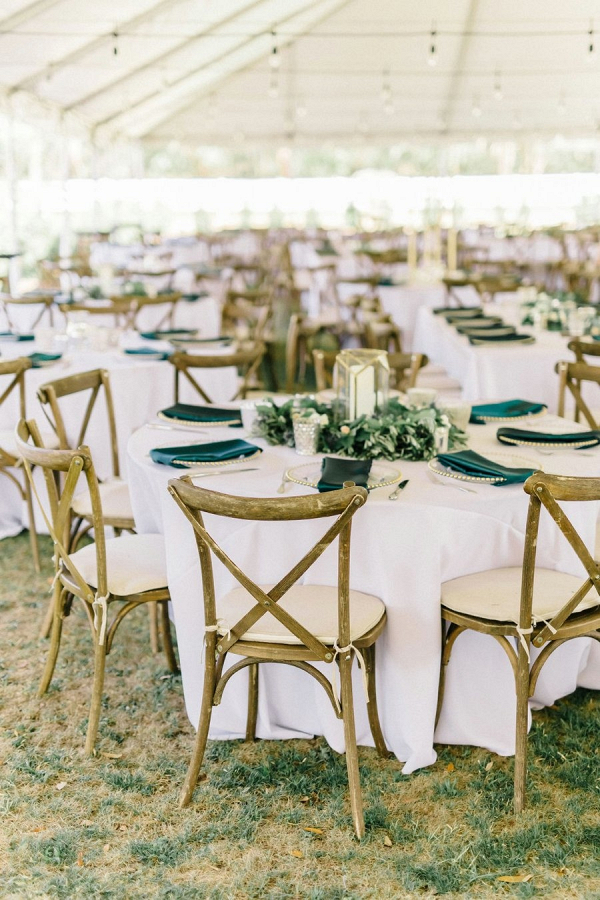 Tented wedding reception with lantern and greenery wreath centerpieces