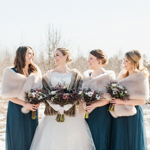 Winter bridesmaids in long tulle teal gowns and fur stoles