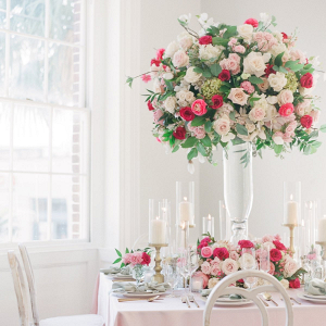 Elegant pink and red wedding table with tall floral centerpiece