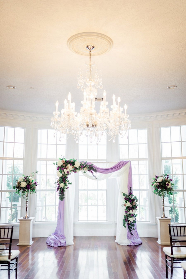 Purple and cream draped ceremony arch