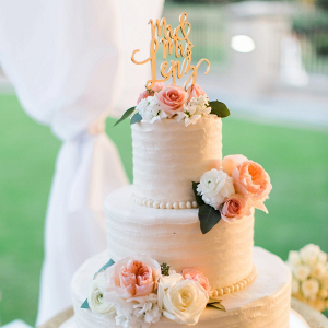 Blush buttercream wedding cake with fresh flowers