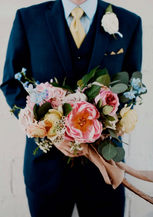 Groom holding bright bouquet on Every Last Detail