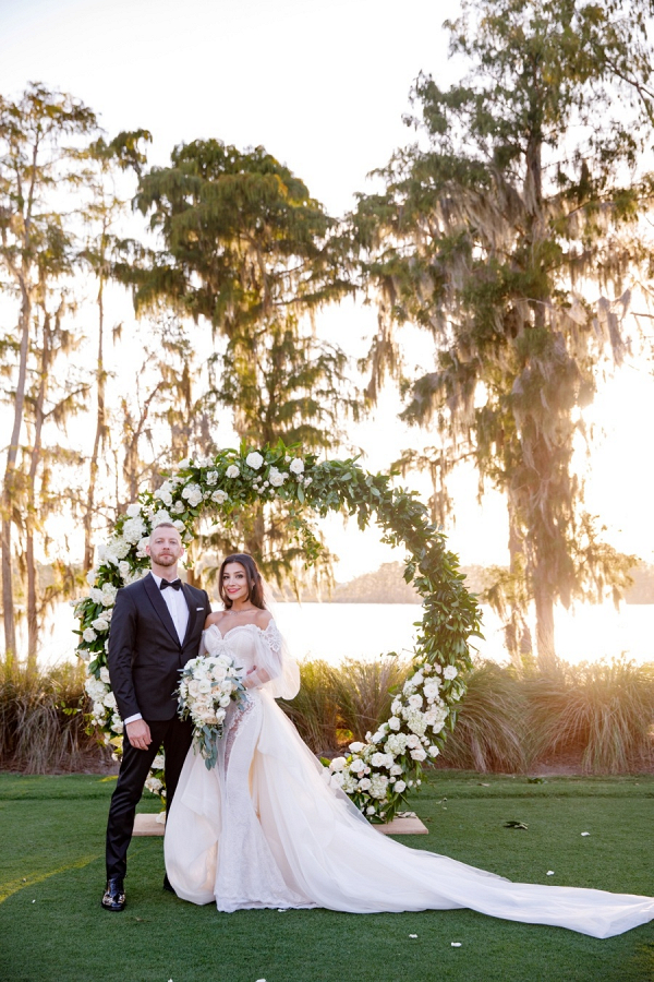 Glam bride and groom with circle arch ceremony backdrop
