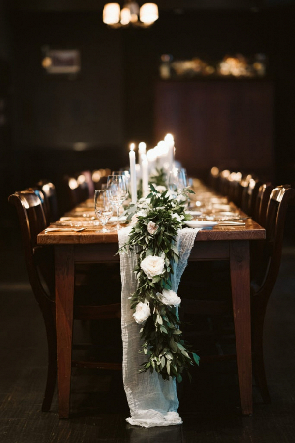 Farm table reception with greenery runner and candles