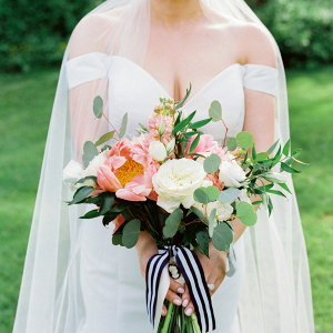 Peach bridal bouquet with navy and white stripe ribbon
