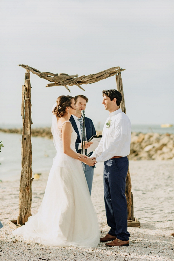 Beach wedding ceremony with driftwood arch