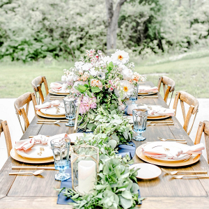 Lush farm table tablescape in gold, pink, and blue