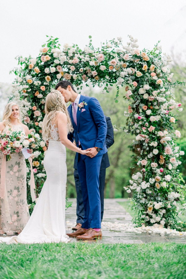 Wedding ceremony with lush floral arch
