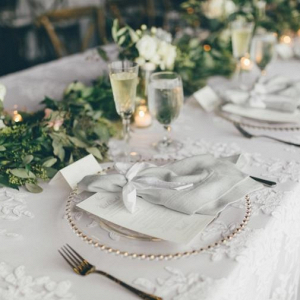 Neutral wedding place setting with garland centerpiece