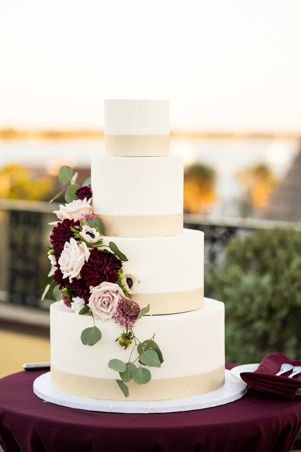 Classic white wedding cake with burgundy and pink fresh florals