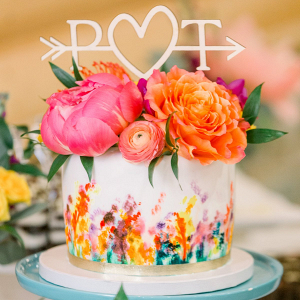Painted wedding cake with fresh flower topper